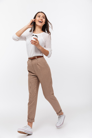 Photo for Portrait of a cheerful asian businesswoman talking on mobile phone while holding cup of coffee to go and walking isolated over white background - Royalty Free Image