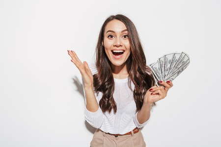 Photo pour Portrait of an excited young asian businesswoman showing money banknotes and celebrating isolated over white background - image libre de droit