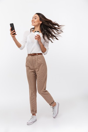 Photo pour Portrait of a cheerful asian businesswoman using mobile phone while holding cup of coffee to go isolated over white background - image libre de droit