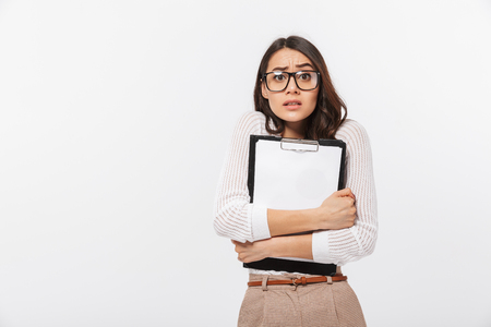Foto de Portrait of a confused asian businesswoman holding blank clipboard isolated over white background - Imagen libre de derechos