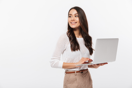 Foto de Portrait of a happy asian businesswoman holding laptop computer iand looking away solated over white background - Imagen libre de derechos