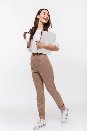 Photo for Full length portrait of a happy asian businesswoman carrying laptop computer and cup of coffee to go while walking isolated over white background - Royalty Free Image