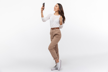 Photo for Full length portrait of a smiling asian businesswoman taking selfie with mobile phone isolated over white background - Royalty Free Image