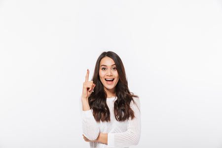 Photo for Portrait of a happy asian businesswoman pointing finger up at copy space isolated over white background - Royalty Free Image
