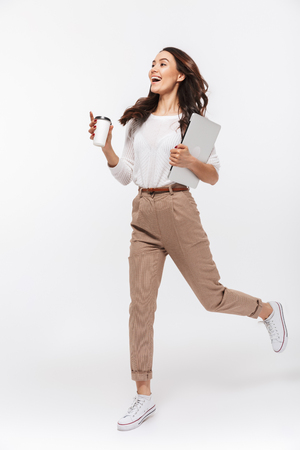 Photo pour Full length portrait of a happy asian businesswoman carrying laptop computer and cup of coffee to go while running isolated over white background - image libre de droit
