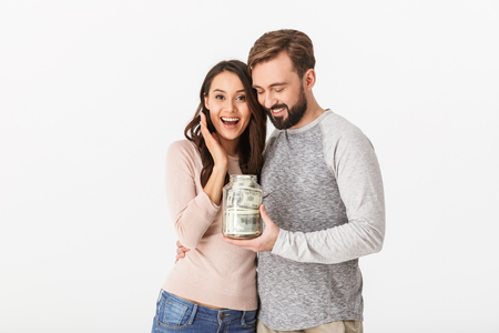 Photo for Image of happy young loving couple isolated over white wall background holding jar with money. - Royalty Free Image