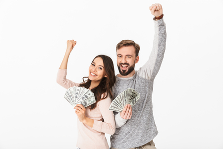 Photo for Photo of happy young loving couple standing isolated over white background holding money make winner gesture looking camera. - Royalty Free Image