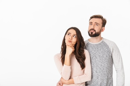 Photo pour Image of serious thinking young loving couple isolated over white wall background looking aside. - image libre de droit