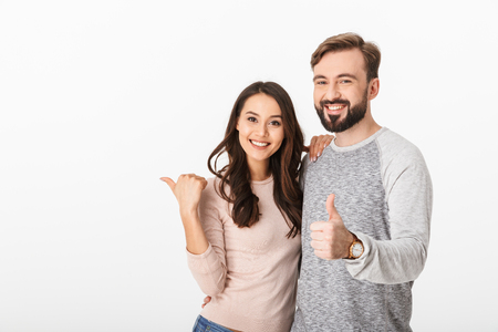 Photo pour Image of cheerful young loving couple isolated over white wall background. Looking camera pointing make thumbs up. - image libre de droit