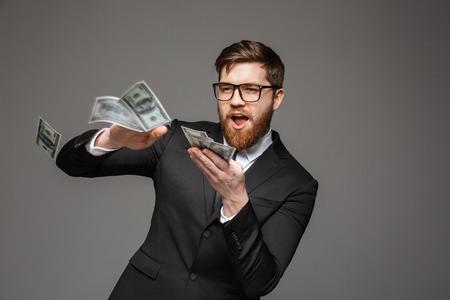 Foto de Portrait of a happy young businessman throwing out money banknotes isolated over gray background - Imagen libre de derechos