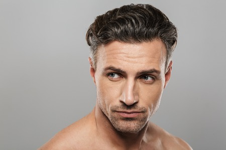 Photo pour Picture of handsome serious mature man standing isolated over grey wall background naked. Looking aside. - image libre de droit