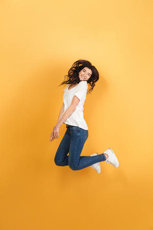 Photo pour Image of young emotional woman jumping isolated over yellow background. Looking camera. - image libre de droit
