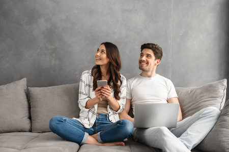 Photo for Beautiful man and woman sitting together on couch in gray interior and looking aside on copyspace while using laptop and smartphone - Royalty Free Image