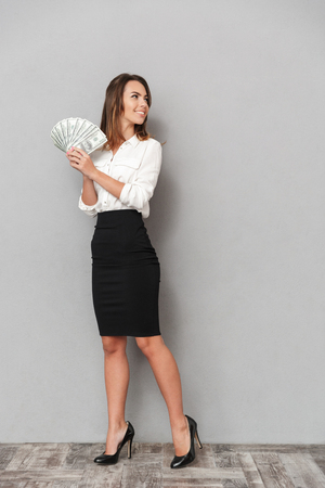 Foto de Photo of excited young business woman standing isolated over grey wall background looking aside holding money. - Imagen libre de derechos