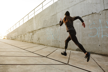 Photo pour Portrait of disabled athlete woman with prosthetic leg in tracksuit running along concrete wall outside - image libre de droit