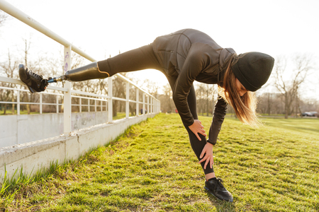 Photo pour Photo of disabled running woman in sportswear doing slopes and stretching prosthetic leg on grass using railing - image libre de droit