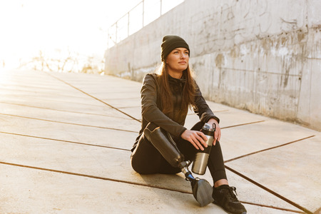 Photo pour Photo of athletic disabled girl with prosthetic leg in sportswear sitting on concrete floor outdoors and looking aside - image libre de droit