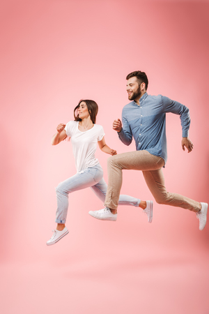 Foto de Full length portrait of a funny young couple running fast isolated over pink background - Imagen libre de derechos
