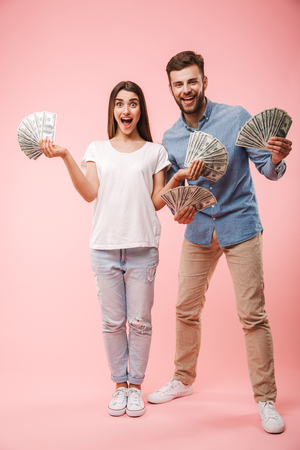 Foto de Full length portrait of a cheerful young couple holding bunch of money banknotes and celebrating success isolated over pink background - Imagen libre de derechos