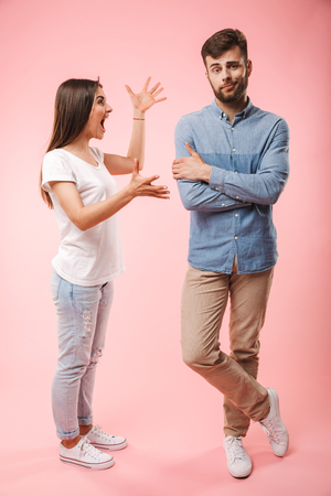 Photo pour Full length portrait of a mad young couple having an argument isolated over pink background - image libre de droit