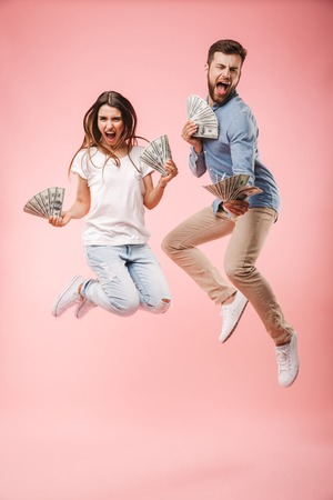 Foto de Full length portrait of an excited young couple holding bunch of money banknotes and celebrating success while jumping isolated over pink background - Imagen libre de derechos