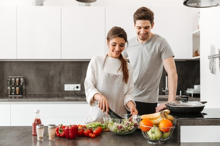 Photo pour Portrait of a cheerful young couple cooking together at the kitchen - image libre de droit
