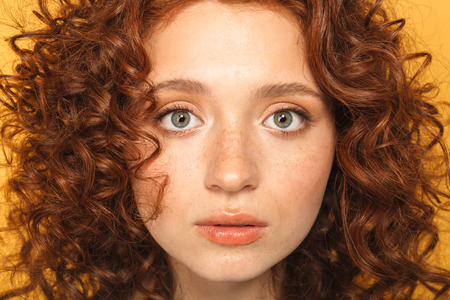 Photo pour Close up portrait of a beautiful curly redhead woman looking at camera isolated over yellow background - image libre de droit