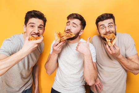 Foto de Three young delighted men eating pizza isolated over yellow background - Imagen libre de derechos