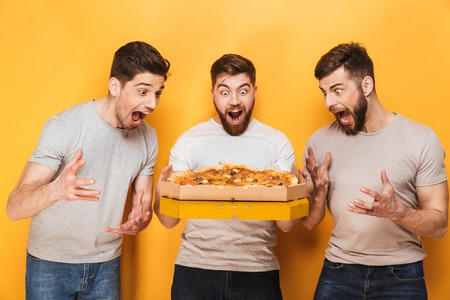 Photo for Three young excited men holding a big pizza isolated over yellow background - Royalty Free Image