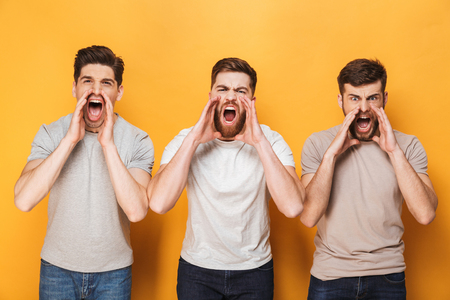 Foto de Three young angry men shouting isolated over yellow background - Imagen libre de derechos
