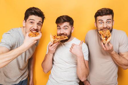 Foto de Three young satisfied men eating pizza isolated over yellow background - Imagen libre de derechos