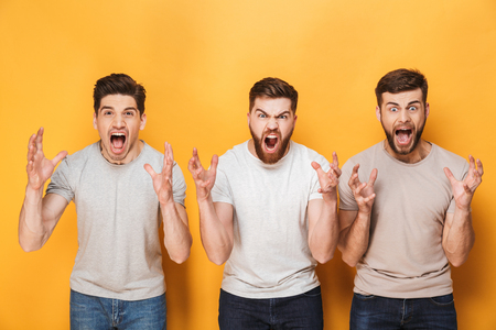 Foto de Three young angry men screaming isolated over yellow background - Imagen libre de derechos
