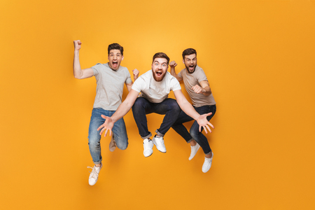 Foto de Three young excited men jumping together isolated over yellow background - Imagen libre de derechos