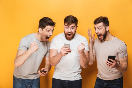 Photo pour Three young smiling men looking at mobile phone and celebrating isolated over yellow background - image libre de droit