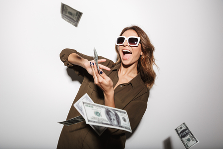 Photo for Portrait of a happy young woman in sunglasses throwing out money banknotes isolated over white background - Royalty Free Image