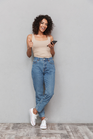 Photo for Full length portrait of a smiling young african woman holding mobile phone and showing thumbs up over gray background - Royalty Free Image