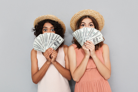 Foto de Portrait of two surprised young women dressed in summer clothes holding money banknotes isolated over gray background - Imagen libre de derechos