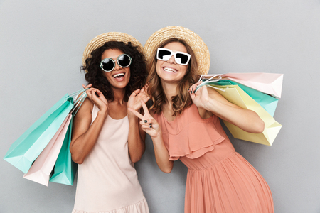 Foto für Portrait of two happy young women dressed in summer clothes holding shopping bags and showing peace gesture isolated over gray background - Lizenzfreies Bild