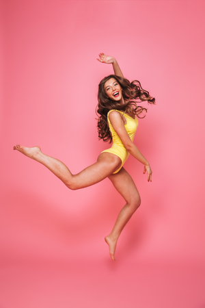 Foto de Full length portrait of a cheerful young woman dressed in swimsuit posing while jumping isolated over pink background - Imagen libre de derechos