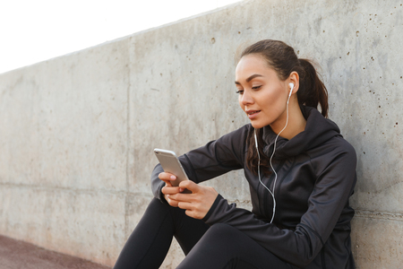 Photo pour Photo of beautiful young asian sports woman sitting outdoors listening music using mobile phone. - image libre de droit