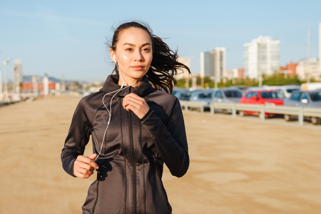 Photo pour Photo of amazing beautiful young asian sports woman running outdoors listening music. - image libre de droit
