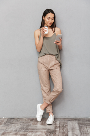 Foto de Full length portrait of a smiling asian woman holding takeaway coffee cup and using mobile phone isolated over gray background - Imagen libre de derechos