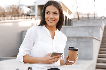 Foto de Smiling brunette woman in shirt sitting outdoors and looking away while holding smartphone and cup of coffee - Imagen libre de derechos