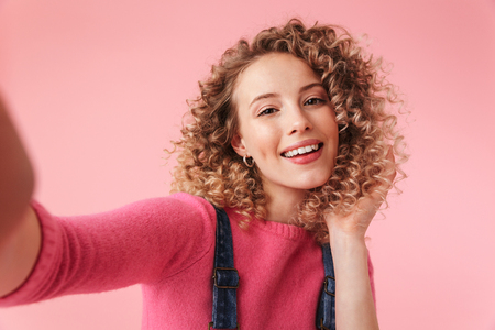 Foto de Portrait of happy young girl with curly hair taking a selfie isolated over pink background - Imagen libre de derechos