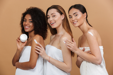 Photo pour Beauty portrait of three young multiracial women with different types of skin: caucasian, african american and asian girls applying cream on body together isolated over beige background - image libre de droit