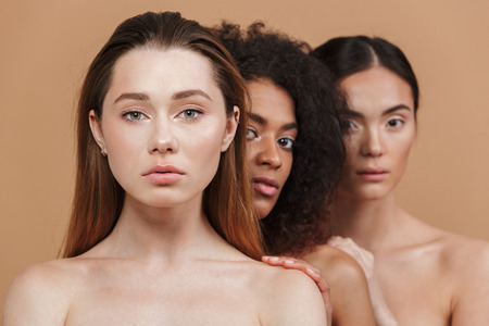Foto de Beauty portrait of three nude women of different nation: caucasian, african american and asian girls standing together isolated over beige background - Imagen libre de derechos