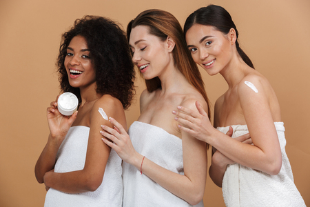 Foto de Beauty portrait of three young multiracial women with different types of skin: caucasian, african american and asian girls applying cream on body together isolated over beige background - Imagen libre de derechos