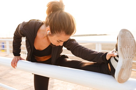Photo pour Image of young sports woman make stretching exercises outdoors on the street listening music. - image libre de droit