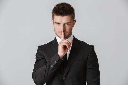 Foto de Portrait of a confident young businessman in suit showing silence gesture isolated over gray background - Imagen libre de derechos