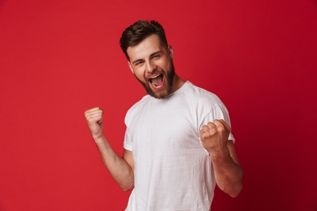 Photo pour Picture of excited young handsome man standing isolated over red wall background make winner gesture. - image libre de droit